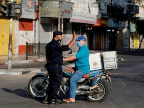 A Palestinian security officer stops a biker in Gaza City early on August 25, 2020 amid a 48-hour lockdown.