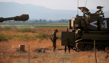 Israeli soldiers gather next to 155 mm self-propelled howitzers in the Upper Galilee in northern Israel on the border with Lebanon on August 2, 2020.