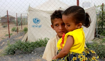 A boy carries his sister as he stands in front of the fence of a closed clinic at a camp for internally displaced people near Abs of Hajjah province, Yemen August 19, 2020.