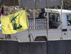 A UN patrol drives past a Hezbollah flag and a concrete barrier in southern Lebanon on the border with Israel, August 26, 2020.