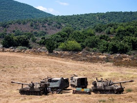 Israeli soldiers sit in a tent next to their mobile artillery piece near the border with Lebanon, northern Israel, Wednesday, Aug. 26, 2020.