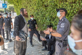 A member of Atra Kadisha confronting a police at the site, August 26, 2020.