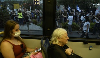 Commuters pass by an anti-Netanyahu protest in a bus in Haifa, northern Israel, August 13, 2020.