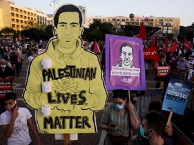 Protesters hold a photo of Eyad Hallaq during a rally against Israel plans to annex parts of the West Bank, in Tel Aviv, Israel, June 6, 2020.