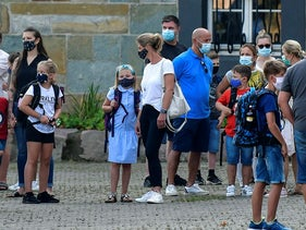 In this Wednesday, Aug. 12, 2020 file photo, parents wait with their children for the start of their first day of school in Gelsenkirchen, Germany