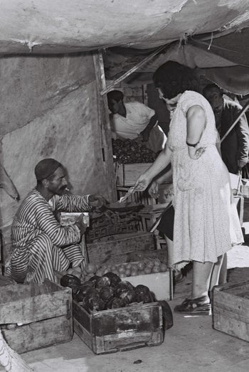 New immigrant Etka Berman, right, buying vegetables in the 1950s.