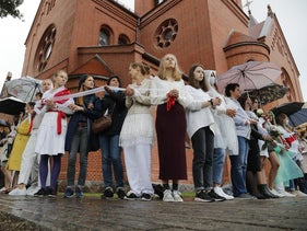 Protesters holding a wait ribbon, a symbol of protest, stand in front of the Church of Saints Simon and Helena during a rally in Minsk, Belarus, August 27, 2020.