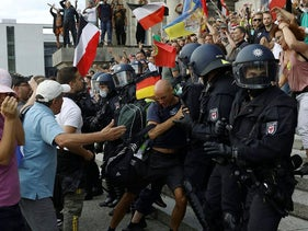 Police officers scuffle with a protester in front of the Reichstag Building during a rally against the government's restrictions following the coronavirus disease (COVID-19) outbreak, in Berlin, Germany, August 29, 2020