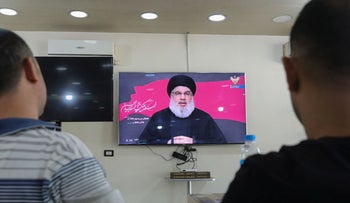 Lebanese men watch the head of the country's Shiite Muslim movement Hezbollah Hassan Nasrallah during a televised speech, Beirut, August 30, 2020