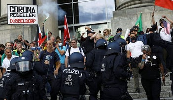 Police officers intervene in front of the Reichstag Building during a rally against the government's restrictions following the coronavirus disease (COVID-19) outbreak, in Berlin, Germany, August 29, 2020. REUTERS/Christian Mang