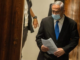 Netanyahu in Knesset August 24, 2020, wearing a black suit, cobalt blue tie, white shirt and a standard blue mask over his nose and mouth, holding papers
