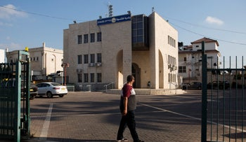 File photo: A man walks past the municipality building in Kalansua, central Israel, September 9, 2019.