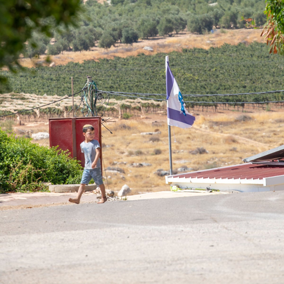 A boy walks through the West Bank settlement outpost of Mitzpeh Kramim, August 28, 2020.