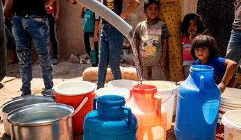 Residents fill up water from cisterns provided by humanitarian organizations during a water outage in Syria's northeastern city of Hasakah on August 22, 2020.