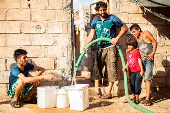 A Syrian man fills up water from cisterns provided by humanitarian organizations during a water outage in Syria's northeastern city of Hasakah on August 22, 2020.