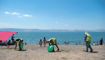 Cleaners collect garbage on a beach on Lake Kinneret, August 28, 2020.