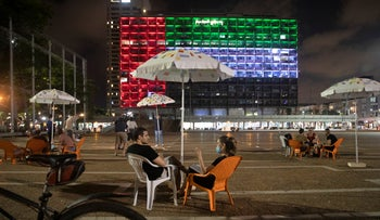 Israelis chat on Rabin Square, in front of Tel Aviv city hall lit up with the United Arab Emirates flag after the announcement of a historic normalization agreement, August 13, 2020.