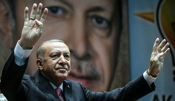 Turkish President Recep Tayyip Erdogan holds up his hand in the 'Rabia' four finger sign first used by pro-Muslim Brotherhood supporters in Egypt. AKP headquarters in Ankara, August 13, 2020.