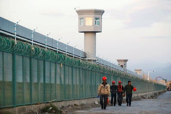 "Workers walk by the perimeter fence of what is officially known as a ""vocational skills education centre"" in Dabancheng in Xinjiang Uighur Autonomous Region, China. September 4, 2018."