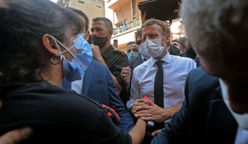 Emmanuel Macron comforts a Lebanese youth during a visit to a heavily damaged neighborhood in Beirut, on August 6, 2020.