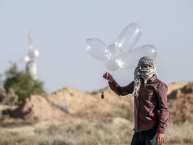 A Palestinian  launches incendiary balloons from the Gaza strip, August 2020.