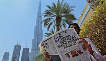 A man in the UAE reads a newspaper announcing normalised ties with Israel. Will the two states cooperate on AI too?