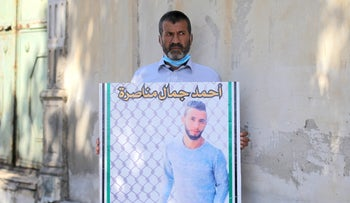 Jamal Manasra, the father of Ahmad Manasra, holding a photo of his son who was killed by an Israeli soldier, Jaffa, August 2020.