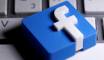 A 3D-printed Facebook logo is seen placed on a keyboard, March 25, 2020.