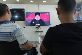 Lebanese men watch Hezbollah's Hassan Nasrallah during a televised speech, at a coffee shop in the southern suburbs of the capital Beirut, August 30, 2020.
