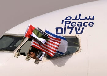 The Emirati, Israeli and U.S. flags are attached to an El Al airplane  adorned with the word 'peace' in Arabic, English and Hebrew, upon its arrival in Abu Dhabi on August 31, 2020.