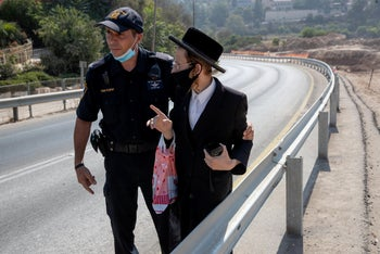A police officer evacuates a protester from an archaeological site where graves were found in Motza, Jerusalem, August 2020.
