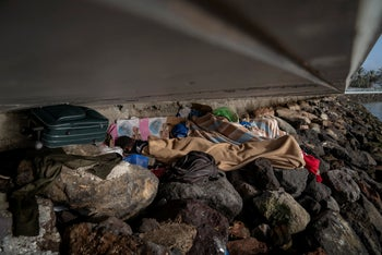 Khalid, a migrant from Gambia, sleeps on a breakwater under a bridge in Gran Canaria island, Spain, on Saturday, August 22, 2020.