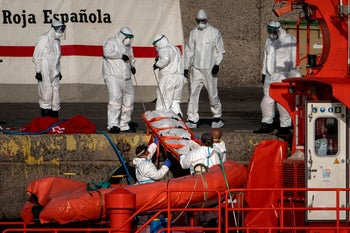 Emergency workers carry a migrant's body after being found dead by the Spanish Maritime Rescue Service, at the Arguineguin port in Gran Canaria island, Spain, on Friday, August 21, 2020.