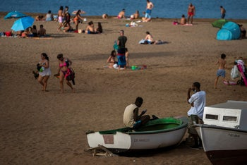 Two migrants sit on a fishing boat as people enjoy the beach in Gran Canaria island, Spain, on Friday, August 21, 2020.