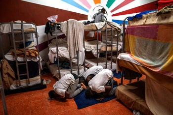Asylum-seekers pray next to their beds at the Modern Christian Mission Church in Fuerteventura, one of the Canary Islands, Spain, on Saturday, August 22, 2020.
