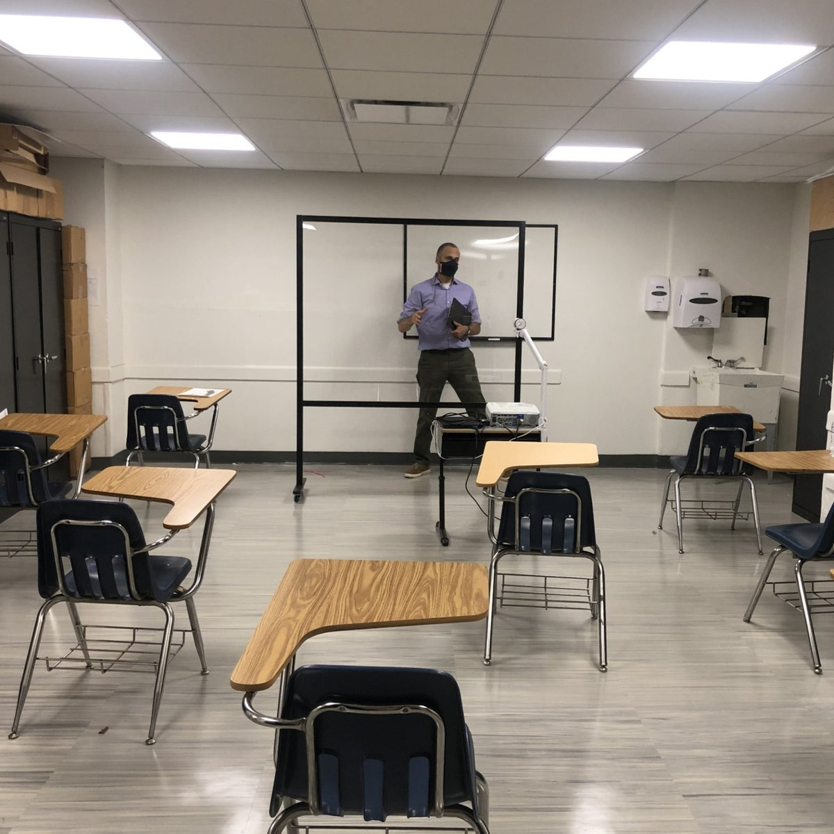 A student's view of a classroom at Kinneret Day School in the Bronx, with the teacher behind a transparent shield.
