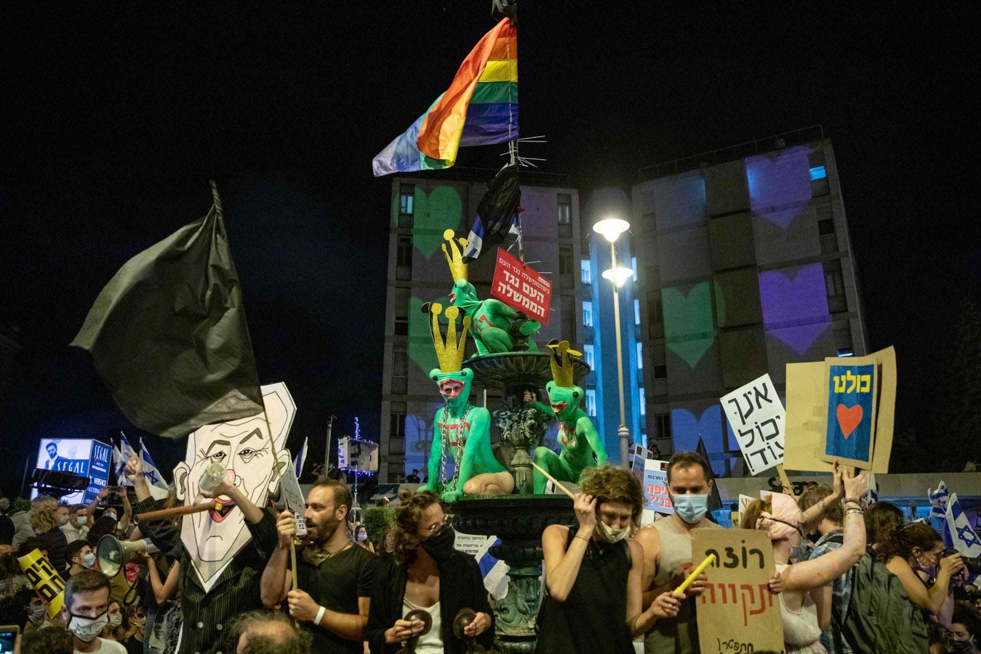 Demonstrators are seen protesting under an LGBT pride flag hanging above the Paris Square in Jerusalem, August 2020.