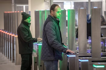 Palestinians have their faces scanned at a West Bank border crossing