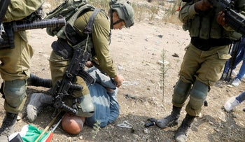 An Israeli soldier detains a Palestinian demonstrator during a protest against Jewish settlements in Jbarah village south of Tulkarm, September 1, 2020.