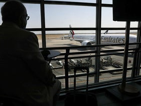 An Emirates plane taxis on the tarmac as a passenger sits at terminal, Iran, July 17, 2020.
