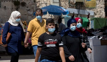 People wearing protective face masks walk in Jerusalem's Old City, September 3, 2020.