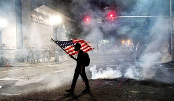 In this July 21, 2020, file photo, a Black Lives Matter protester carries an American flag as teargas fills the air outside the Mark O. Hatfield United States Courthouse in Portland, Ore