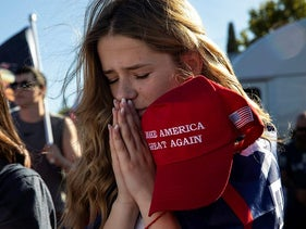 Liza Durasenko, 16, from Oregon City, Ore., prays during a rally in support of President Donald Trump on Saturday, Aug. 29, 2020, in Clackamas, Ore.