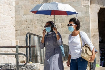 A nun shelters from the sun in the baking Old City of Jerusalem