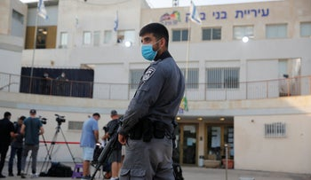 An Israeli Police officer stands in front of the Bnei Brak municipality, designated a 'red' city, September 6, 2020.