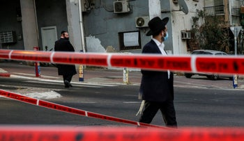 Ultra-Orthodox men walking near a police cordon in the central Israeli city of Bnei Brak, September 6, 2020.
