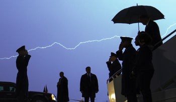 Lightning streaking across the sky as President Donald Trump walks down a set of stairs from Air Force One carrying an umbrella as he arrives at Andrews Air Force Base, August 28, 2020.