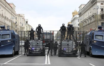 Belarusian law enforcement officers standing guard behind barriers during an opposition rally to protest against police brutality and to reject the presidential election results, Minsk, September 6, 2020.