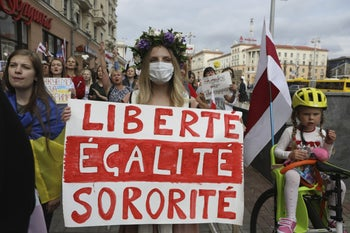 Women with old Belarusian national flags and a poster, echoing the national motto of France, during an opposition rally to protest the official presidential election results, Minsk, September 5, 2020.