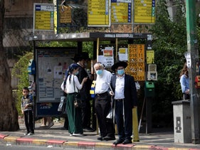 Members of the ultra-Orthodox community stand at a bus stop in Bnei Brak, September 8, 2020.